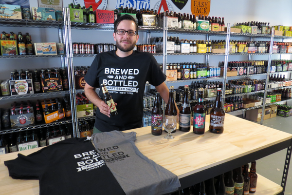 Chris Budde, owner of Brewed and Bottled Craft Beer Shop, stands in front of his vast wall of beer. The new Village of Lewiston shop will open Friday with a special event.