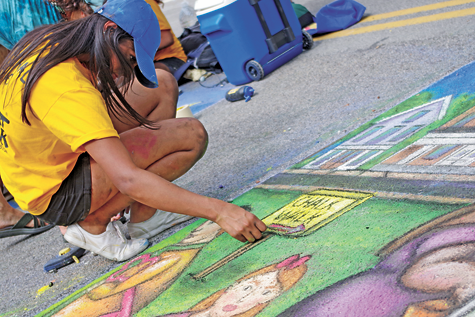 Lovepreet Kaur puts the finishing touches on Grand Island's chalk mural at the Chalk Walk competition.
