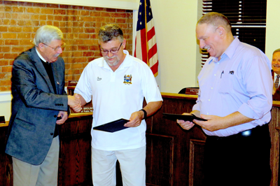 Mayor Terry Collesano, far left, presented DPW Superintendent Terry Brolinski (center) and DPW mechanic Robert Crewe with certificates recognizing 25 years of service to the municipality.
