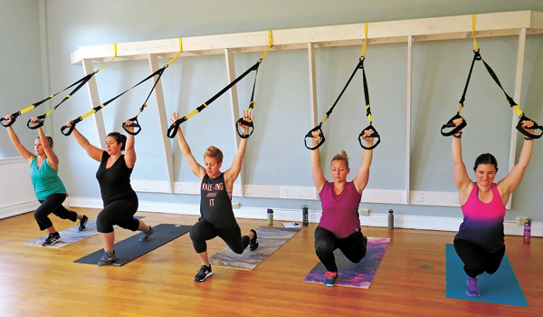 Ami Patrick works with her `rock stars` in a Thursday morning TRX class. She is also shown below.