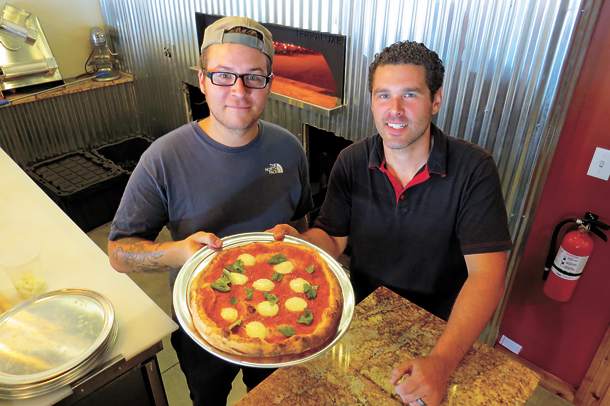 Gallo Coal Fire Kitchen chef David Murphy, left, and proprietor/manager Michael Hibbard hold up a freshly made hearth-fired pizza pie.