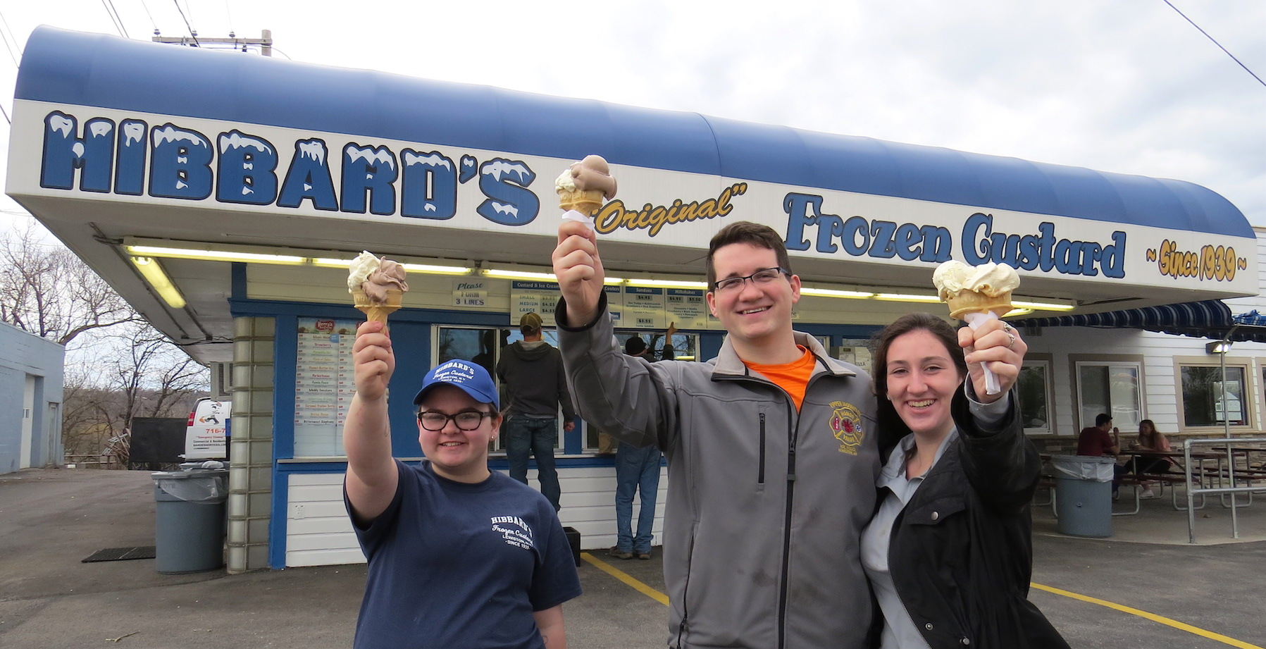 Max Jacobson of Lewiston and Emily Virgil of Rochester celebrate their first Hibbard's Original Frozen Custard stop of the season on Monday. Employee Gabby Ott joins them outside the stand.