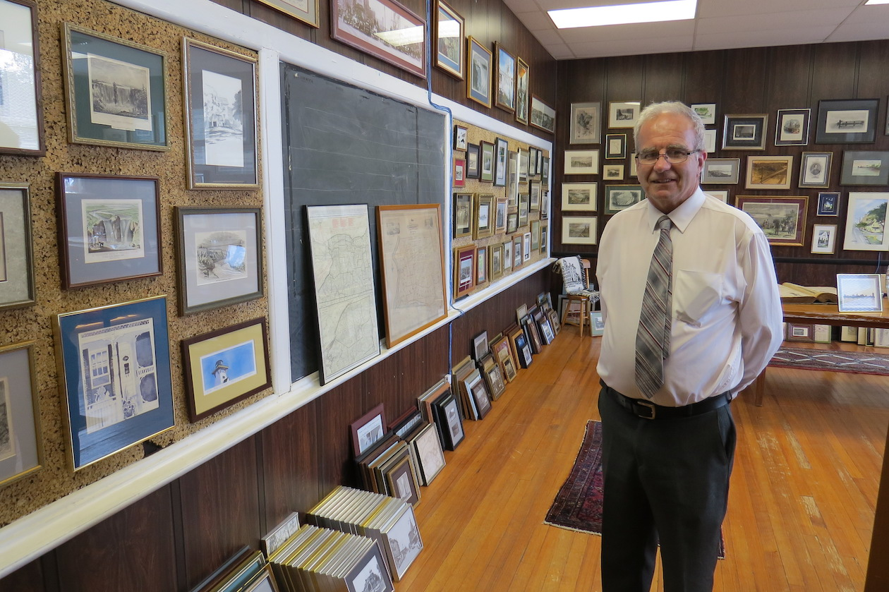 Russell H. Piper Jr. is shown inside the Red Brick with several of the historical items he's loaned to the Village of Lewiston.