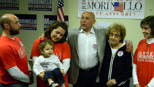 The Hon. Angelo Morinello, center, flanked by family members, thanks supporters in Niagara Falls after his Assembly election victory Tuesday. (Photo by Terry Duffy)