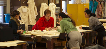 Suzannah Emerson, Old Fort Niagara's music coordinator, left, and Marilyn Deighton, Niagara University associate professor, center left, work with students who are sewing waistcoats.