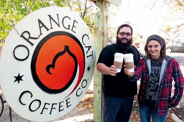 Matthew Garcia and Mary Vaughan salute customers outside of Orange Cat Coffee Co. on Center Street in Lewiston. The popular business is offering 10 percent off all bulk coffee and tea purchases made on Small Business Saturday, Nov. 26. (Photo by Joshua Maloni)