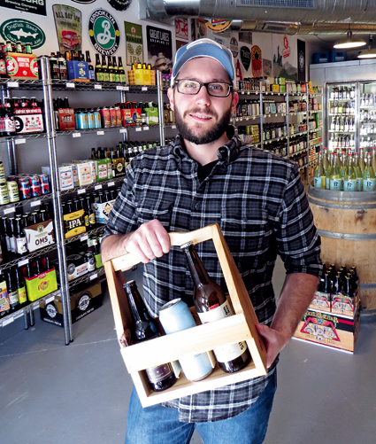 Chris Budde displays a locally made holder, which will be on sale on Small Business Saturday, Nov. 26, at Brewed and Bottled, located at the corner of Center and North Fourth streets, Lewiston.