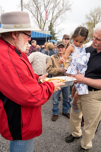 Larry Balch offers some smelt to a youngster waiting in line.