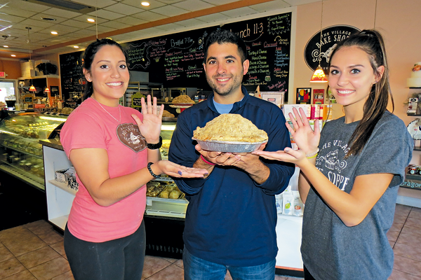 Village Bake Shoppe owner Mike Fiore is flanked by employees Annmarie Catalano and Corrinna Dompkowski, who proudly wave a `5` to signify the restaurant's anniversary.