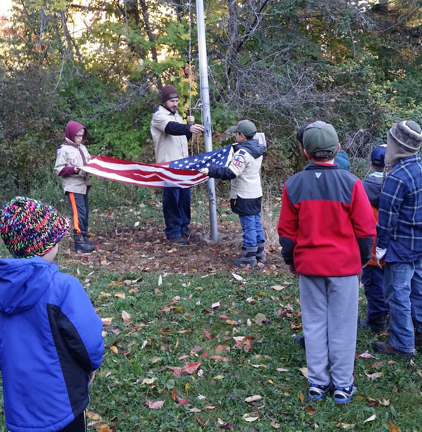Scouts from Cub Scout Pack 829 in Youngstown raise the flag at an overnight camping adventure last October. The group invites first- through fifth-grade boys and their families to learn more about Cub Scouts. (Photo by Charlotte Clark)