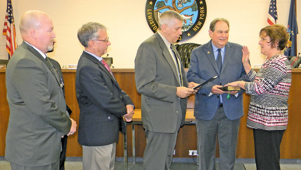 Newly elected Town Councilwoman Beth Ceretto was sworn-in Monday by Town Councilman Ron Winkley as Supervisor Dennis Brochey and board members look on. Holding the Bible is her husband, John, a former Lewiston councilman, now assemblyman for the 145th District. At right, she receives congratulations from the group.