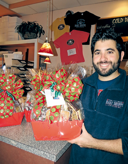 "The Village Bake Shoppe's Mike Fiore holds one of his store's holiday baskets. Starting next week, ""We switch gears from pies and all of our Thanksgiving desserts to jumping right into our Christmas baskets, cookie trays - shipping those out for our commercial customers all over the country,"" he said."