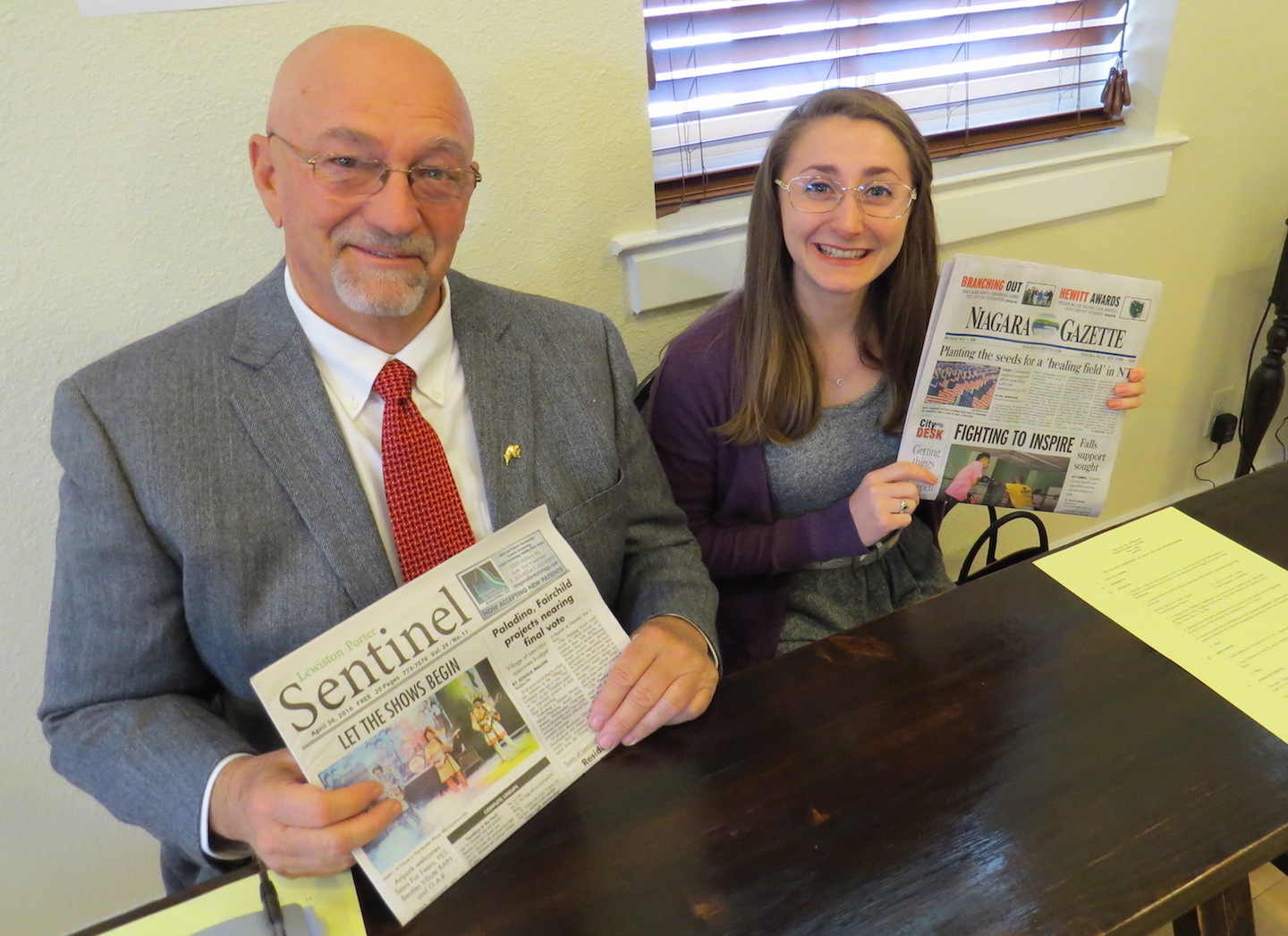 Bruce Sutherland, sitting in Joshua Maloni's seat, holds a copy of The Sentinel, while Joan McDonough, a reporter for the Niagara Gazette, hold a copy of her newspaper.