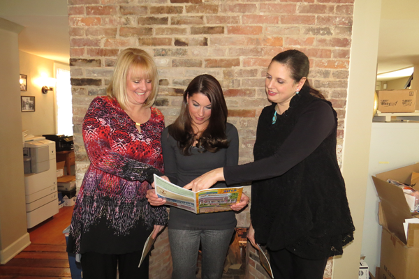 Pictured, from left, with the booklet: Chamber of Commerce Director of Finance and Insurance Suzanne Raby, Administrative Assistant Erica Wirth and President Jennifer Pauly.