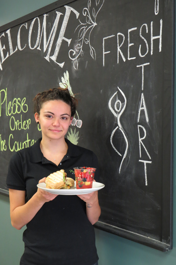 Carly Farruggia holds the bacon breakfast sandwich and a side of fruit.