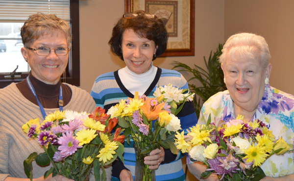 Niagara Hospice volunteers, from left, Mary Dixon, Karen Feger and Sylvia Cooper, start to `think spring` as they help prepare for the annual Niagara Hospice spring bouquet sale.