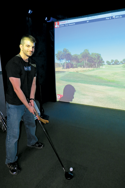 Jonathan Simon plays the golf simulator at Lewiston Event Center.