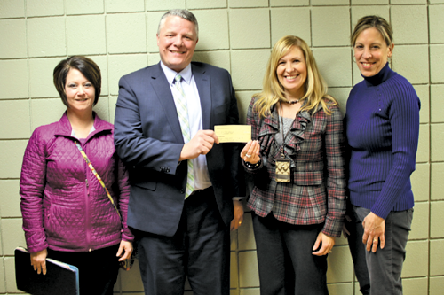 PEC PTA representatives Christine Barrientos (left) and Melissa Eoute (right) present a $12,000 check to Lewiston-Porter principals (center) Andrew Auer and Tamara Larson. (Photo by Janet Schultz)