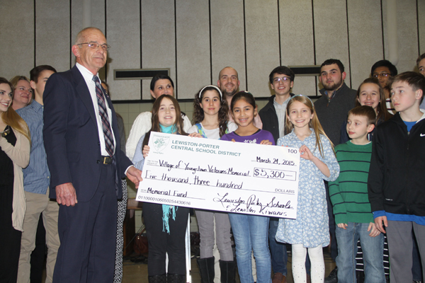 Youngstown Mayor Raleigh Reynolds accepted a check for $5,300 from the Lewiston-Porter students at Tuesday's meeting. The funds will be used to repair the Veterans Memorial in Youngstown that was ruined by vandals earlier this year. Students raised the funds by selling wristbands. The Kiwanis Club of Lewiston matched the amount. (Photo by Janet Schultz)