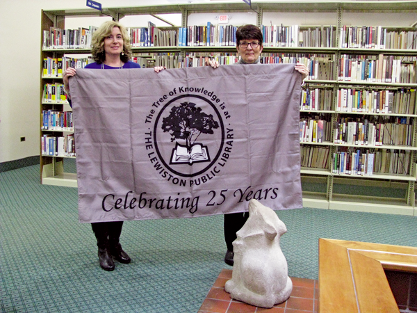 Jill Palermo, director of the Lewiston Public Library, and JoAnne Lotterio, president of the Friends of the Lewiston Public Library, display one of the flags to be displayed this year as part of the celebration of the library's 25th anniversary at its current location. (Photo by Susan Mikula Campbell)