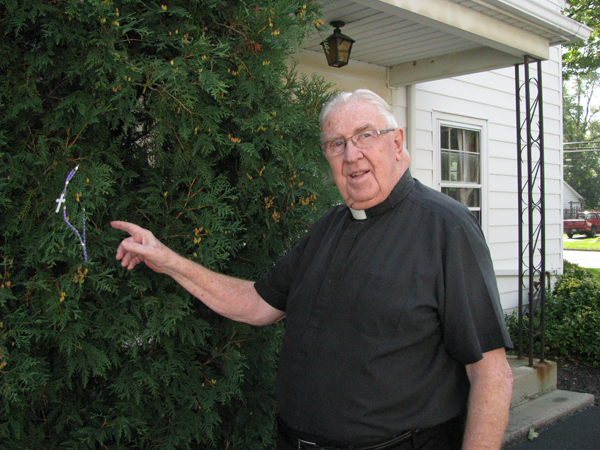 Monsignor J. Thomas Moran is shown at his residence in Youngstown pointing out the rosary on the bush outside his home. It's an old tradition to pray this way for good weather for an event.