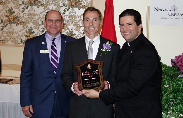 Dr. Roger Klatt, superintendent for the Barker and Royalton-Hartland central school districts, receives the 2014 Educational Leader of the Year Award from Dr. Timothy Downs, provost, and the Rev. James J. Maher, C.M., president.