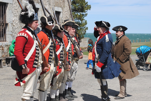 `Enemies conversing`: Old Fort Niagara's British Redcoats meet face-to-face with an officer of the Continental Army, portrayed by event organizer Tommy Thompson of Hoisington's New York Rangers, and an American militiaman, portrayed by Tony Consiglio, also of Hoisington's, during a prior Patriots Day Weekend event. (Photo by Charlotte Clark)