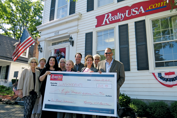 Pictured, from left: RealtyUSA staffers Sharon Gadacz, Judy Perriello, Gail Ventry, Karen Salhany, Linda Wenz, Leo Notaro, Gina Gigliotti (manager) and Richard Portale with Chris Kreiger of WNY Heroes.