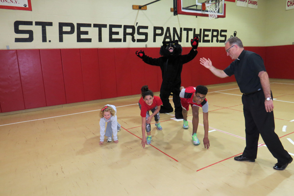 Second-grader Isabella Violante (far left) and seventh-graders Rosie Franjoine and Julian Andreola are pictured practicing with the Rev. Msgr. David LiPuma as Peter the Panther (aka eighth-grader Harrison Abramaitys) cheers them on.