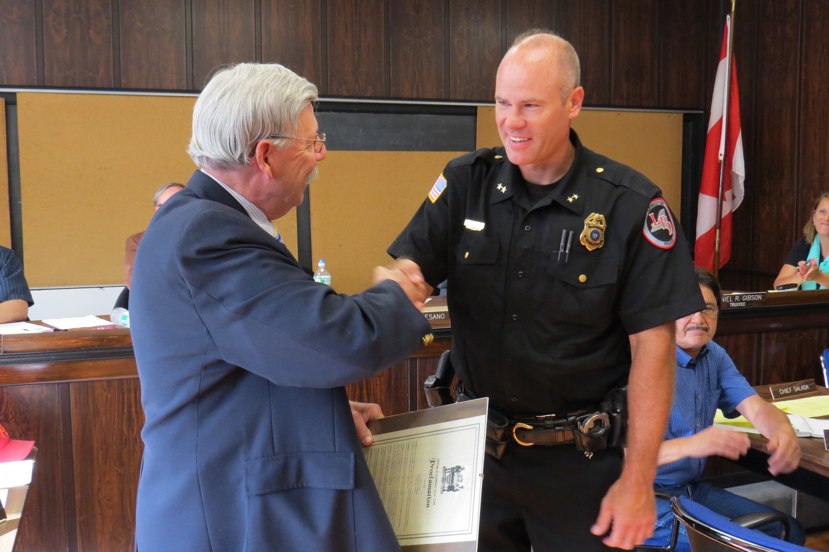 Mayor Terry Collesano congratulates retiring LPD Chief Chris Salada during a board meeting jULY 20.