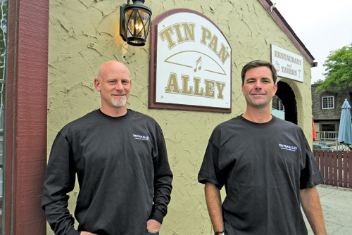Eric Matthews, left, and Ken Bryan stand in front of Tin Pan Alley, the village restaurant they've owned for 20 years.