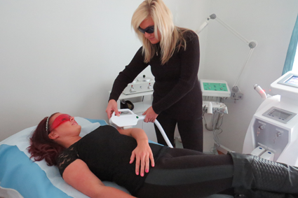 Tuscana Salon & Spa laser tech and esthetician Erica Browning scans Bridgit Sherman's skin.