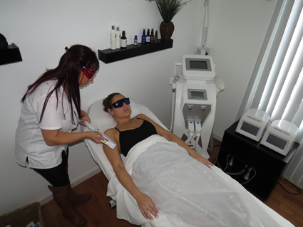 Stephanie Hancock runs Tuscana Spa's YAG laser over owner Jillian Zaccarella's skin.