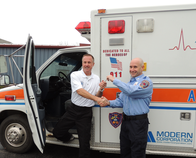 Greg Sitek (right), president of Upper Mountain hands the keys of the fire company's donated ambulance over to Alex Parmelee, operations manager of San Pedro Emergency Services.