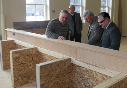 Trustee Vic Eydt, left, explains the wood carving on the new village dais to Mayor Terry Collesano and Engineer Mike Marino.