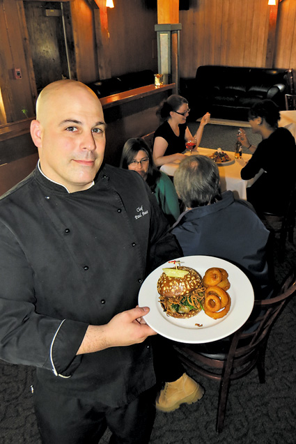 Water Street Landing chef Paul Bunce holds up the River SideBar's ghost pepper cheeseburger, which is paired with crispy onion rings (also shown inset with a plate of duck nachos).