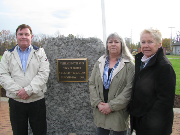 Shown at the Veterans Memorial in Youngstown, from left are: Youngstown Trustee Tim Adamson; Anne Brett, Town of Porter Historical Society museum director; and Dotty Riordan, Town of Porter Historical Society president.