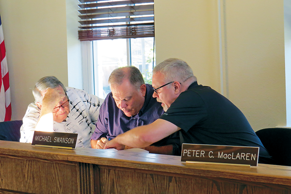 Zoning Board members George VanHoose, Bart Klettke and Michael Swanson review proposal plans prior to Thursday's special meeting.