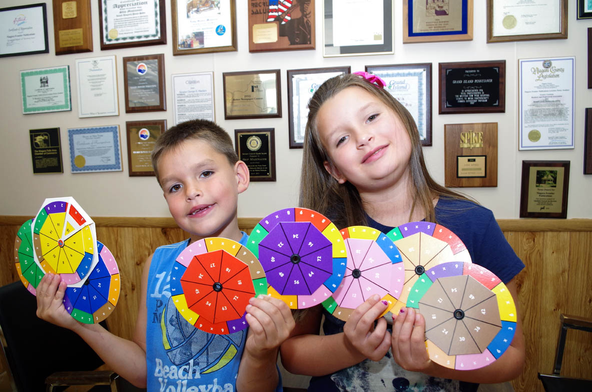 Alannah Kaifas-Concha, 8, and Fermin Concha, 7, learn multiplication with The Fact Wheel, a product of Islander Shirley Barberic.
