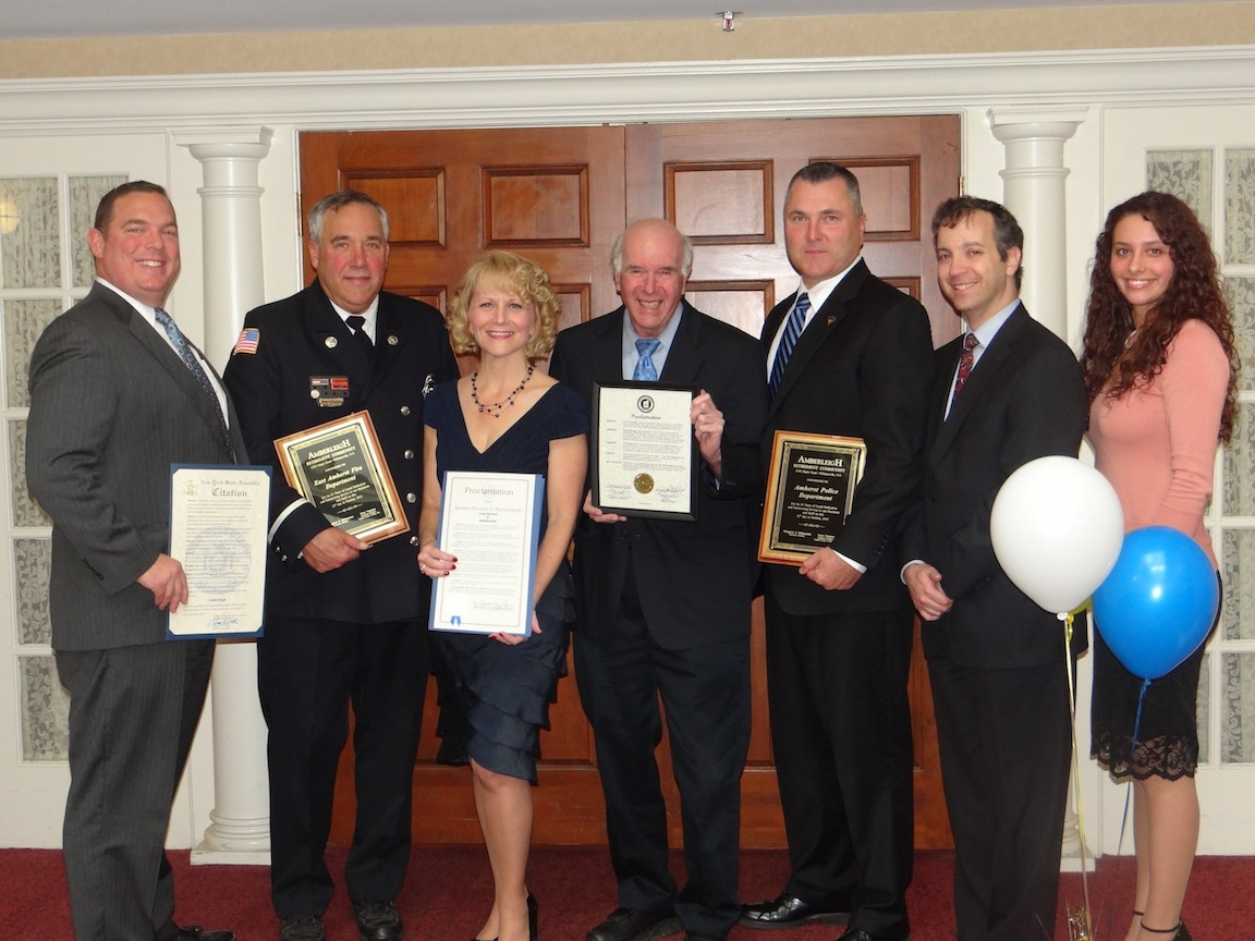 Assemblyman Ray Walter, East Amherst Fire Department firefighter Robert Hart, Amherst Supervisor Dr. Barry Weinstein, Amherst Police Department Chief John Askey, Amherst Councilmember Steven Sander and State Sen. Michael Ranzenhofer's representative, Rachel Koremski, stand with Amberleigh Retirement Community Executive Director Margaret Kleinmann (center) during the 25th anniversary celebration on Oct. 25.