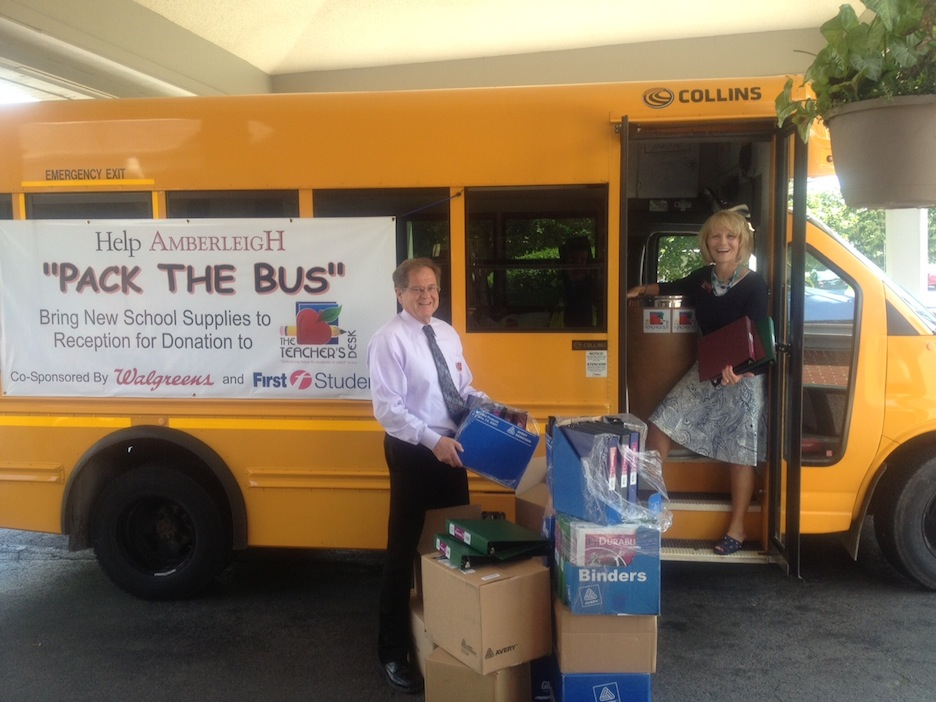 Margaret Kleinmann, executive director of Amberleigh Retirement Community, and Jim Coats, assistant director, load a bus donated by First Student with school supplies to be donated by the community and its residents for delivery to The Teacher's Desk. The supplies will be distributed to teachers for children in most need.