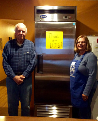 Divine Mercy Food Pantry volunteers Stan Krajkowski and Kathleen Camcemi stand in front of their new refrigerator.