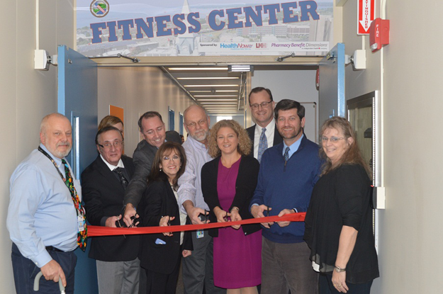 Erie County Executive Mark C. Poloncarz (second from right) is joined by partners from the Labor-Management Healthcare Fund, BlueCross BlueShield of WNY, and Pharmacy Benefits Dimensions along with Erie County employees to cut the ribbon on the new fitness center for county employees at the Edward A. Rath building. The fitness center will be available at no cost to county employees.