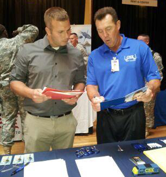 Ryan Camman, a veteran from Buffalo, speaks with Steve Toomey, senior job recruiter for CSX Transportation during a `Hiring our Heroes` job fair held last year at the Connecticut Street Armory.