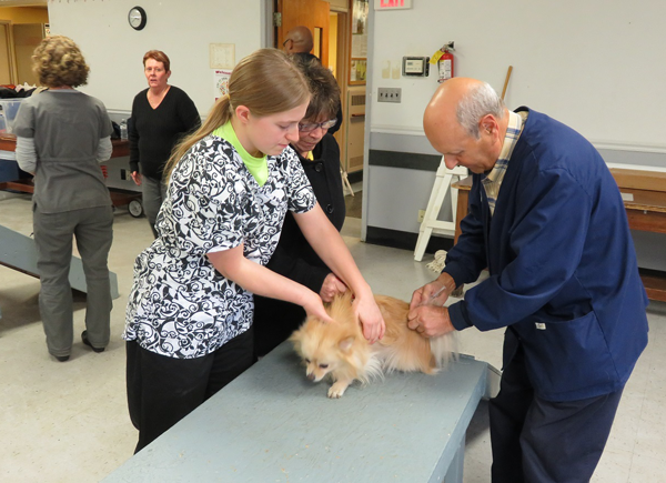 Dr. Joe Savarese from the Medaille College veterinary technology program joins one of his students in administering rabies vaccine to one of the 412 dogs that were protected at the free January clinic.