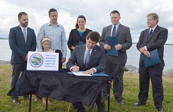Erie County Executive Mark C. Poloncarz (at podium, seated at table) is flanked by environmental advocates and Erie County legislators, as Erie becomes the first county in New York to enact legislation prohibiting the sale of microbead-containing products.