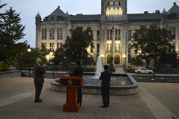 Erie County Executive Mark C. Poloncarz (at podium) is joined by Erie County Legislator Joseph Lorigo (10th district, at right) and Public Works Commissioner John Loffredo applauded as the lights came on at Old Erie County Hall.