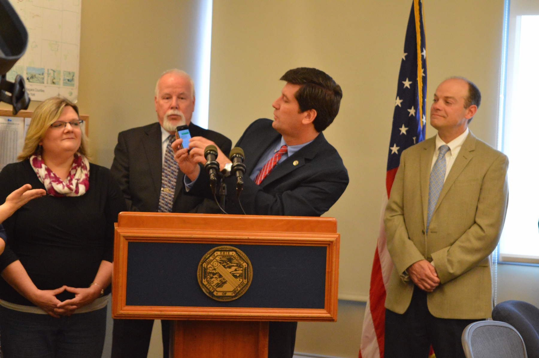 Erie County Executive Mark C. Poloncarz (at podium, with phone) sends the first official text to 9-1-1 in Erie County Wednesday. Looking on, from left, are Pamela Rohring, president emeritus of Deaf Access Services; Erie County Commissioner of Central Police Services John Glascott; and Executive Director of the Erie County Office for the Disabled Frank Cammarata.