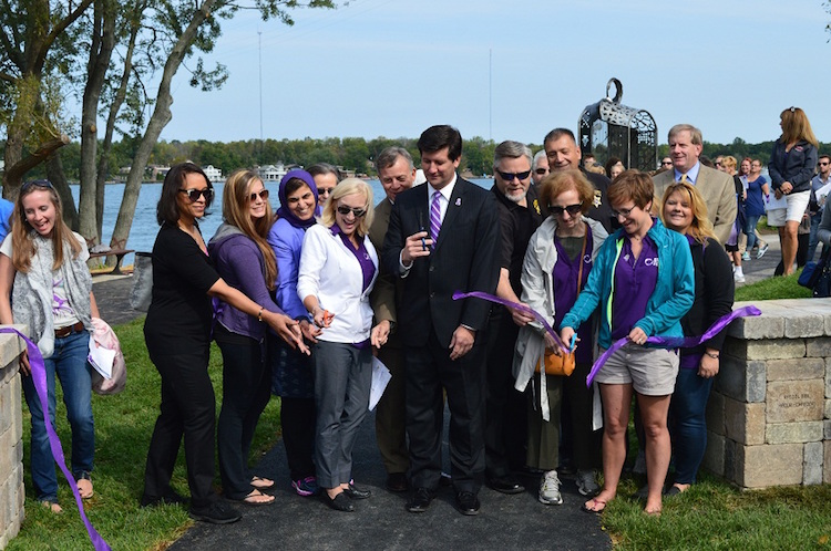 Erie County Executive Mark C. Poloncarz (center) joins Commissioner of Public Advocacy Sawrie Becker (on right) and community partners in cutting the ribbon at the Domestic Violence Tribute Garden in Isle View Park. The Tribute Garden provides a place for peaceful, quiet reflection for individuals and families whose lives have been touched by domestic violence.