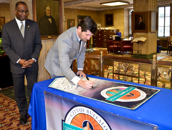 Erie County Executive Mark C. Poloncarz signs the Buffalo Opportunity Pledge as Buffalo Mayor Byron Brown looks on. More than 5,100 individuals and 210 businesses representing over 70,000 employees have signed the pledge, which aims to encourage businesses and communities to work together to build a culture of inclusion and fairness.